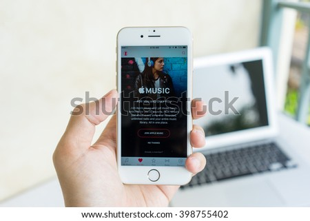 MAE HONG SON, THAILAND - MARCH 13, 2015: Apple music the world largest internet music app on smartphone device screen with hand holding on Apple iPhone 6S.