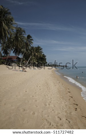 MAE NAM BEACH, KOH SAMUI, THAILAND - AUGUST 2016: White sand beach of Mae Nam in Koh Samui, Thailand, with the first relaxing tourists of the morning.