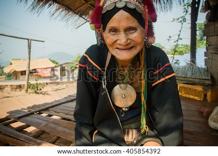 MAE SALONG,  CHIANG RAI, THAILAND - MAY 2, 2005 :  North of Thailand during summer. An old woman from the Akha ethnic group rests in the shadow of her house, the temperature can reach 40 degrees .  - stock photo