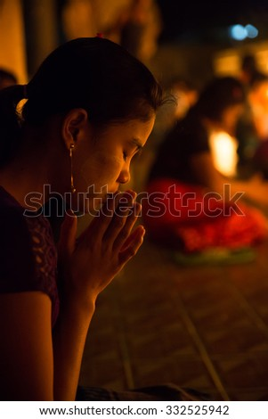 MAE SOT, TAK, THAILAND - OCTOBER28, 2015 : Unidentified Myanmar woman praying to the  Buddha statue on the end of Buddhist Lent festival at Wat Thai Watthanaram, Mae Sot, Tak, Thailand