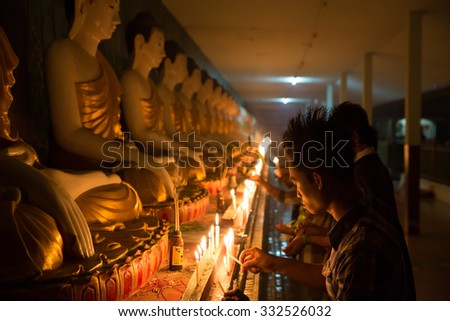 MAE SOT, THAILAND - OCTOBER28, 2015 : Unidentified Myanmar migrant workers lighting candles to worship the Buddha  on the end of Buddhist Lent festival at Wat Thai Watthanaram, Mae Sot, Tak, Thailand