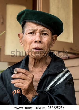 MAE TAN NOI, THAILAND - MARCH 22 2015: Elderly Thai man sits and smokes at remote train station Mae Tan Noi in Northern Thailand. - stock photo