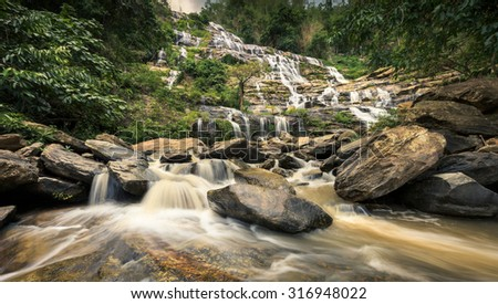 Mae Ya Waterfall is one of the most beautiful cascades in Doi Inthanon, Chiang Mai. Water flows from a 280-metre steep cliff onto different rock formations in a lower basin, creating a beautiful scene - stock photo