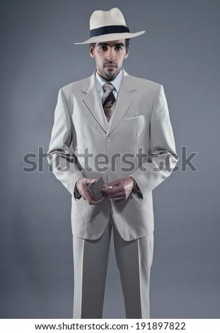 Mafia fashion man wearing white striped suit and hat. Holding vintage cigarette box. Studio shot. - stock photo