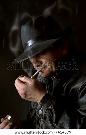 Mafia watchman lighting a cigarette in the dark - stock photo