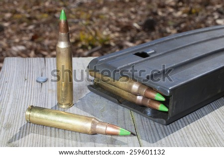 Magazine on wood planks with green tipped metal ammo - stock photo