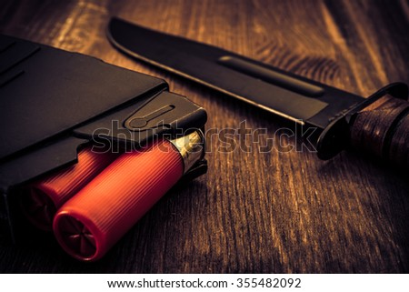 Magazine with red cartridges 12 gauge and combat knife on the wooden table. Close up view, image vignetting and the yellow-blue toning - stock photo