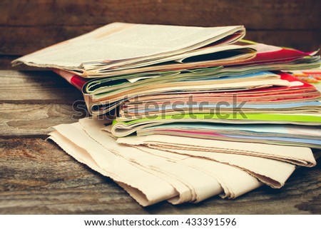 Magazines and newspapers on old wood background. Toned image - stock photo