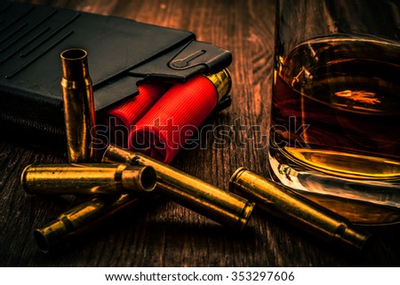Magazines with red cartridges 12 gauge and glass of whiskey on the wooden table. Close up view, image vignetting and the orange-blue toning - stock photo