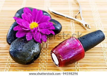 Magenta nail polish, cuticle cutters, black stones, and magenta color flower. - stock photo