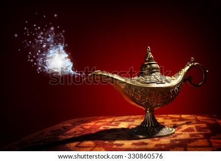 Magic lamp from the story of Aladdin with Genie appearing in blue smoke concept for wishing, luck and magic - stock photo
