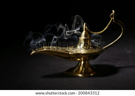Magic lamp isolated on black - stock photo