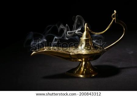 Magic lamp isolated on black - stock photo