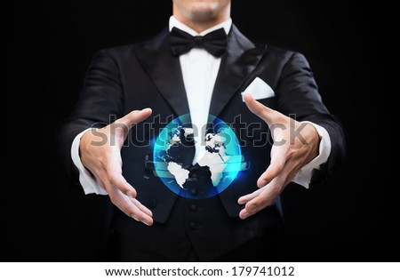 magic, performance and future technology concept - magician in top hat showing globe hologram - stock photo