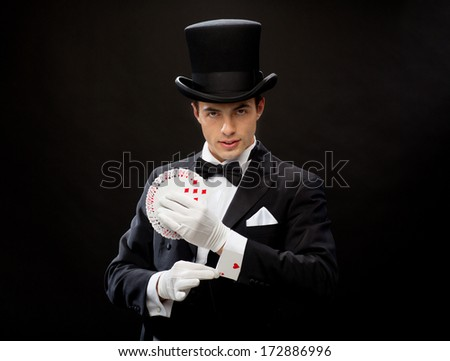 magic, performance, circus, gambling, casino, poker, show concept - magician in top hat showing trick with playing cards - stock photo