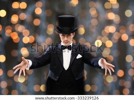 magic, performance, circus, people and show concept - magician in top hat showing trick over nigh lights background - stock photo