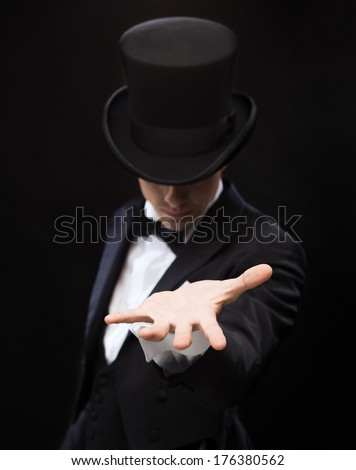 magic, performance, circus, show and advertisement concept - magician holding something on palm of his hand - stock photo