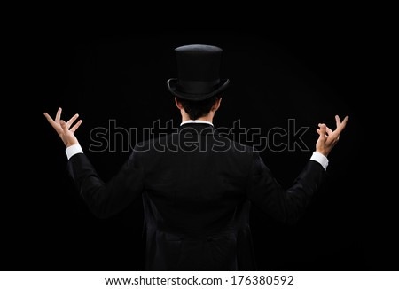 magic, performance, circus, show concept - magician in top hat showing trick from the back - stock photo