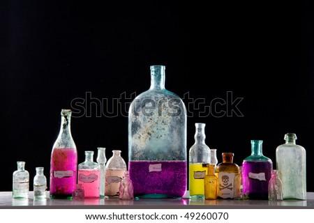 Magic spells in antique bottles over black background - stock photo