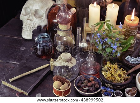 Magic still life with skull, vintage bottles, book, herbs and candles on witch table. Old pharmacy, esoteric or alternative medicine concept. Medieval alchemist ritual - stock photo