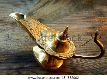 Magical genie lamp isolated on a wooden background - stock photo