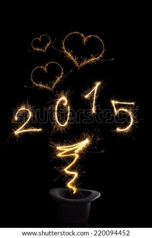 Magical happy new year. Magical fireworks from black top hat forming digits 2015, heart shapes and abstract light lines isolated on black background. Happy new year background. - stock photo