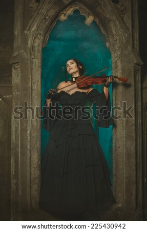 Magical medieval girl playing the violin at night in the opening window of the castle. - stock photo