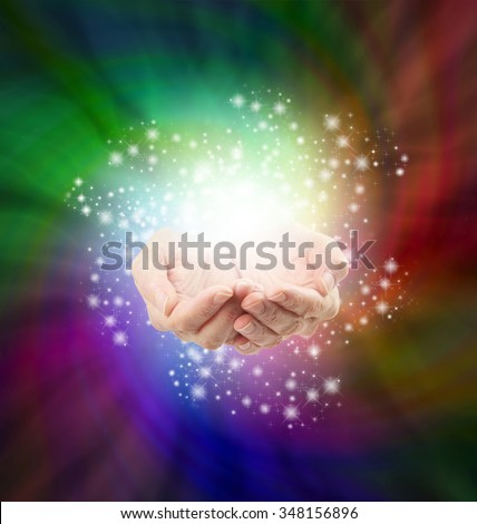 Magical Moment - Female cupped hands emerging from a spiraling dark multicolored background with a twirl of sparkles all around depicting magic and spells  - stock photo