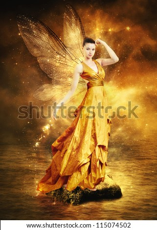 Magical young woman as golden fairy with wings - stock photo