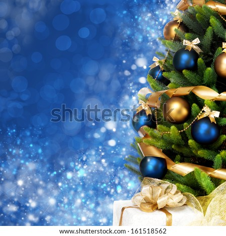 Magically decorated Christmas Tree with balls, ribbons and garlands on a blurred blue shiny, fairy and sparkling background - stock photo