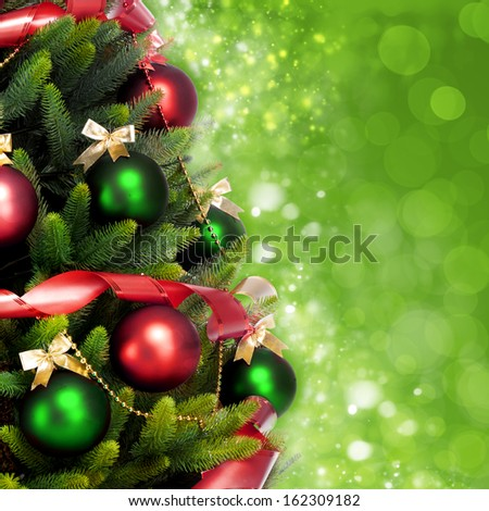 Magically decorated Christmas Tree with balls, ribbons and red garlands on a blurred green shiny, sparkling and fairy background - stock photo