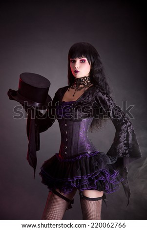 Magician assistant in purple and black gothic Halloween outfit, studio shot on black background  - stock photo