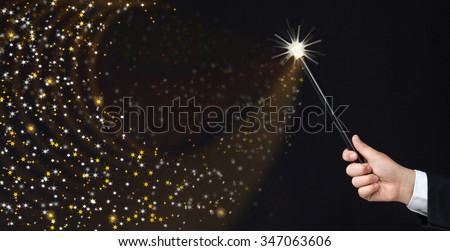 Magician hand conjuring sparks on black background - copy space with magic - stock photo