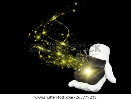 magician hand in white glove holding opened antique box with a yellow magic blown from inside - stock photo