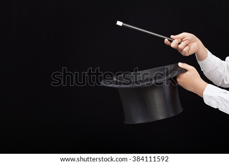 Magician hands with magic hat and wand pointing to copy space on the left