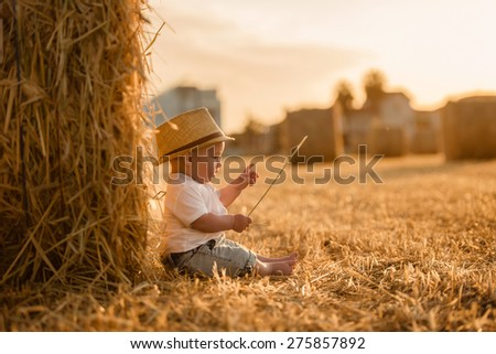 magician kid, a little boy sitting in a field with stacks at sunset - stock photo
