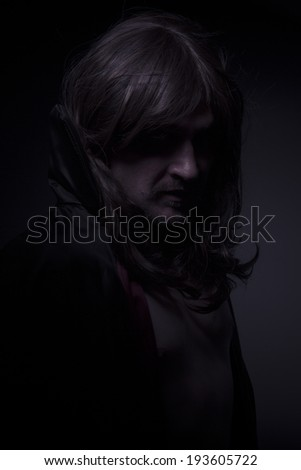Magician, man with long hair and black coat - stock photo