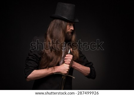 Magician performing a magic trick with sword. Long-haired bearded man in black suit. - stock photo