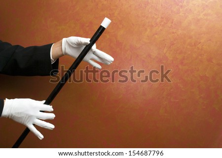 Magician performing with wand - stock photo