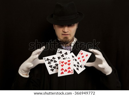 Magician show with playing cards.  Isolated on black background - stock photo