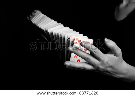 magician showing his trick with deck of cards on black background - stock photo
