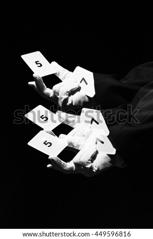 Magician waving his hand. In hand he has a playing cards. Sleeve is a playing card with the number seven. Photo taken with a long exposure time and used stroboscopic flash. Includes a effect. - stock photo
