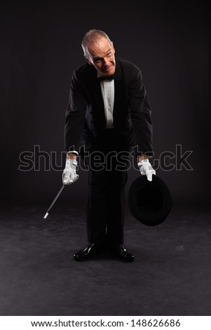 Magician with black suit and hat holding a magic stick. Studio shot against black.