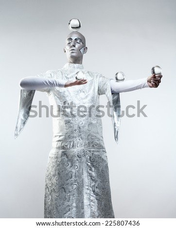Magician with Glass Balls in Stage Makeup and Costume - stock photo