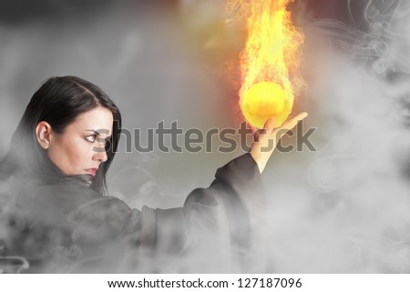 Magician woman with a fire ball in her hands - stock photo