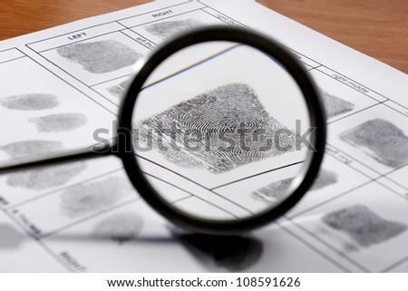 Magifying glass inspecting a fingerprint. - stock photo