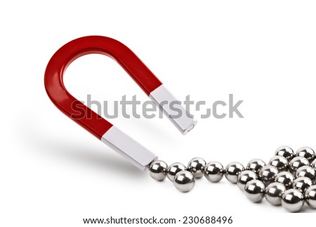 Magnet attracting chrome ball bearing concept for marketing, business leadership or attracting clients - stock photo