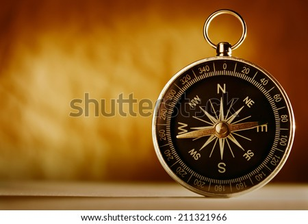Magnetic compass against an old brown vintage background with a highlight and copyspace in a conceptual image of navigation, adventure and travel - stock photo