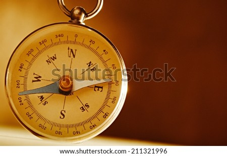 Magnetic compass against an old brown vintage background with a highlight and copyspace in a conceptual image of navigation, adventure and travel