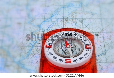 Magnetic compass is located on a topographic map. A map with a compass. - stock photo